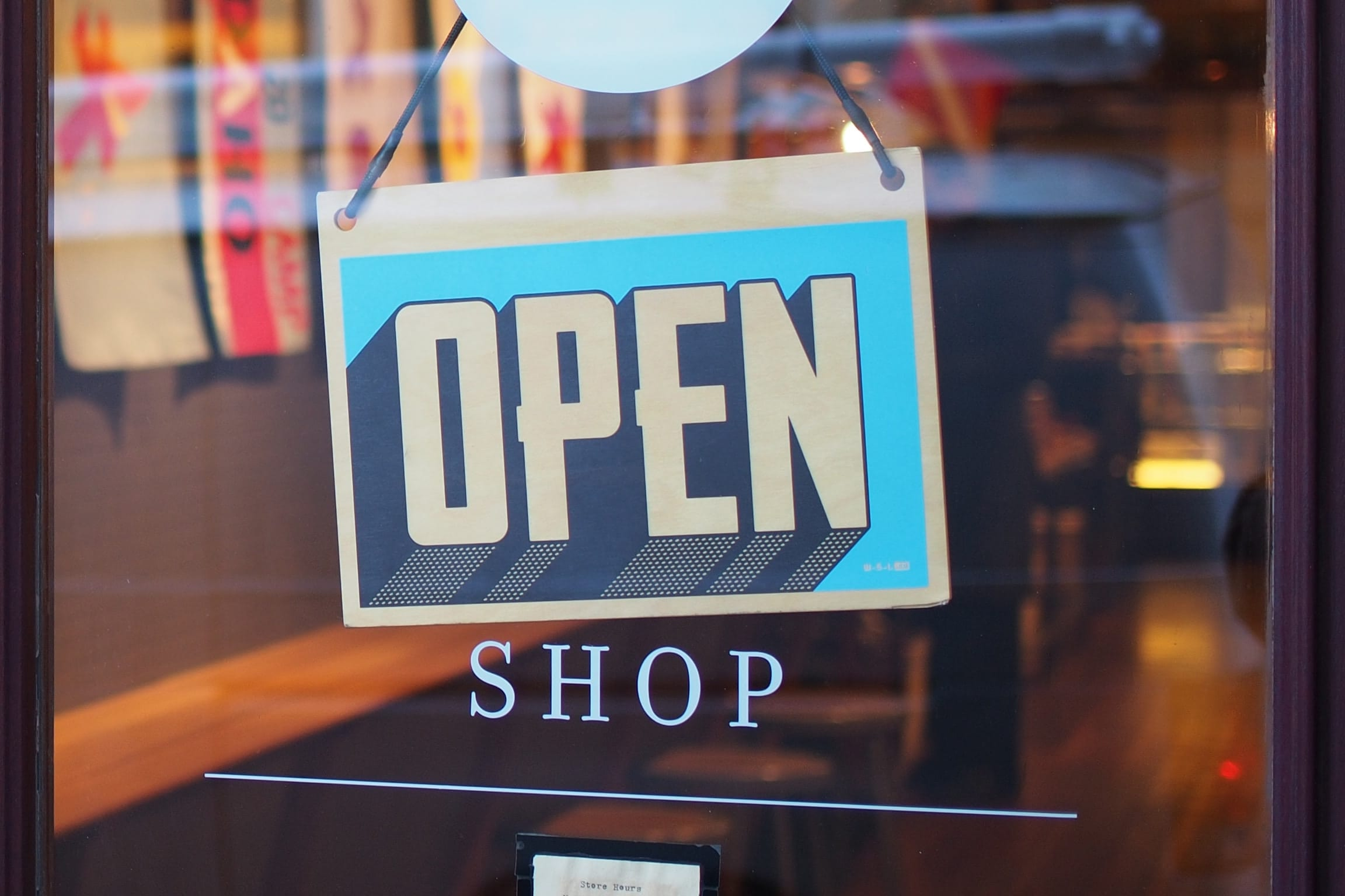 "Grey and blue ""Open"" sign hanging in shop window; image by Mike Petrucci, via Unsplash.com."