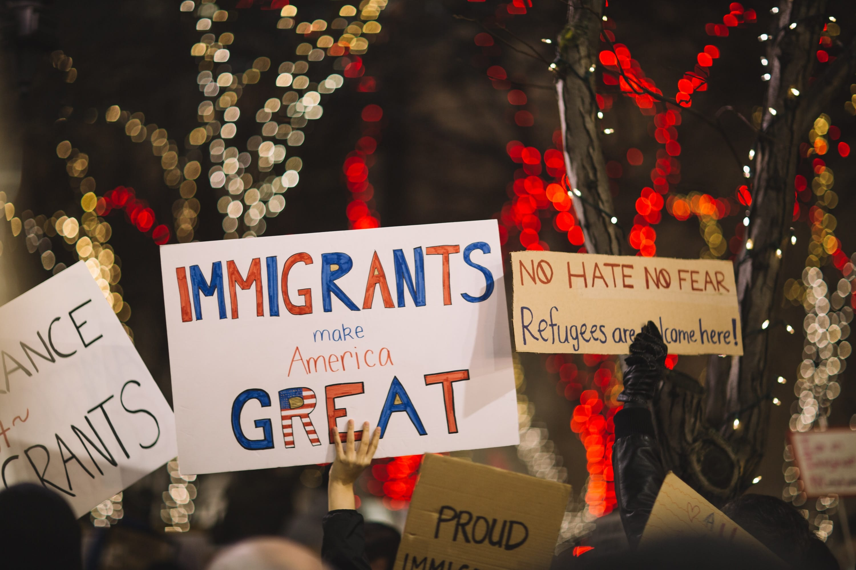 """Sign saying """"Immigrants make America Great"""" and one saying """"No Hate, No Fear, Refugees are Welcome here;"""" image by Nitish Meena, via Unsplash.com."""