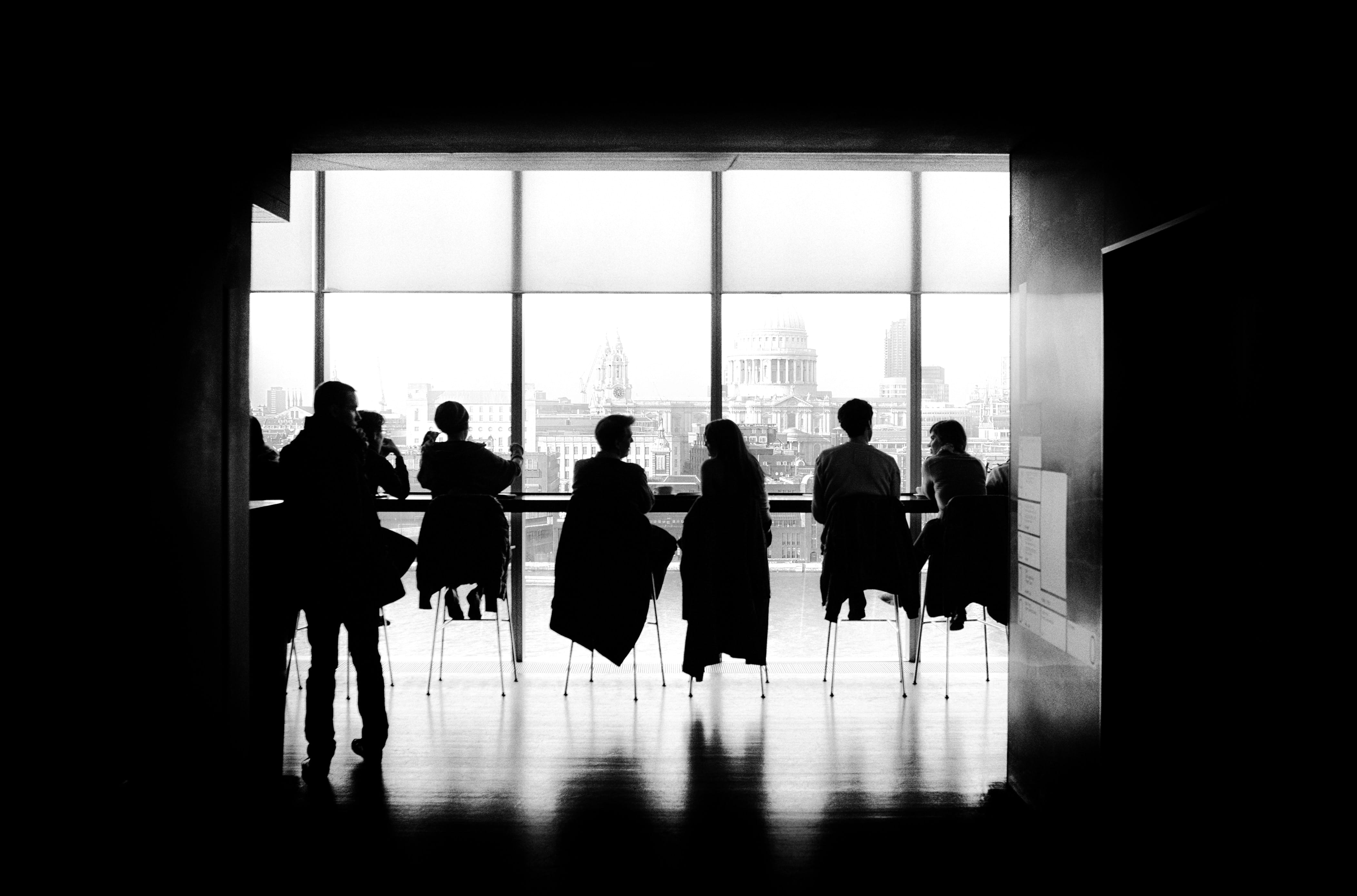 People sitting at a long conference table in front of windows; image by Samuel Zeller, via Unsplash.com.