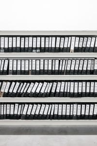 A shelf of binders full of paperwork; image by Samuel Zeller, via Unsplash.com.