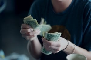 Woman counting cash; image by Sharon McCutcheon, via Unsplash.com.