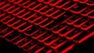 Computer keyboard with black keys backlit in red; image by Taskin Ashiq, via Unsplash.com.