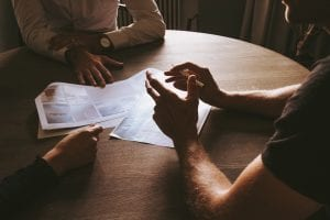 Three people at a table reviewing paperwork; image by Thomas Drouault, via Unsplash.com.