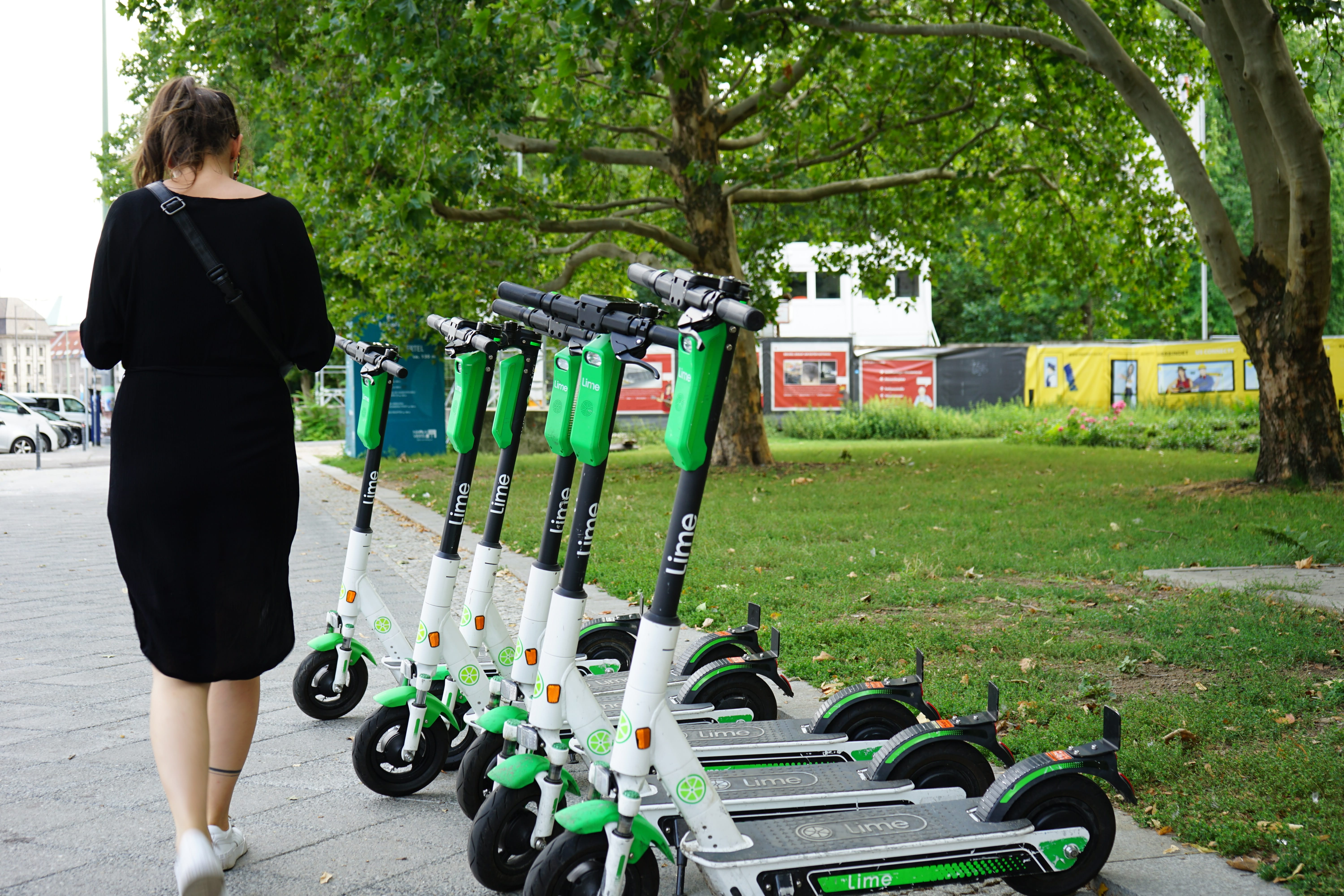 Woman walking past row of Lime eScooters; image by Vince Jacob; via Unsplash.com.