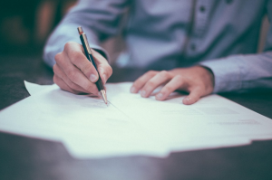 Man in blue dress shirt writing on paperwork; image by Helloquence, via Unsplash.com.