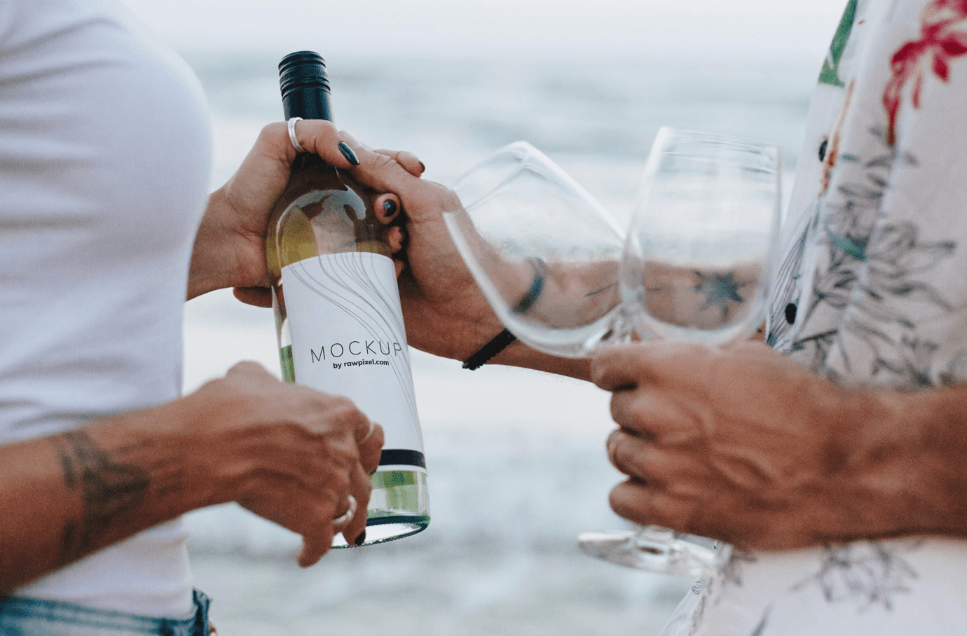 Man and woman holding hands and a bottle of wine with glasses; image by rawpixel.com from Pexels.com.