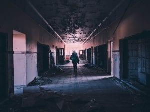 Person walking in darkened hallway; image by Andrew Amistad, via Unsplash.com.