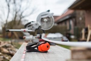 Red and black earmuffs next to miter saw; image by Cetteup, via Unsplash.com.