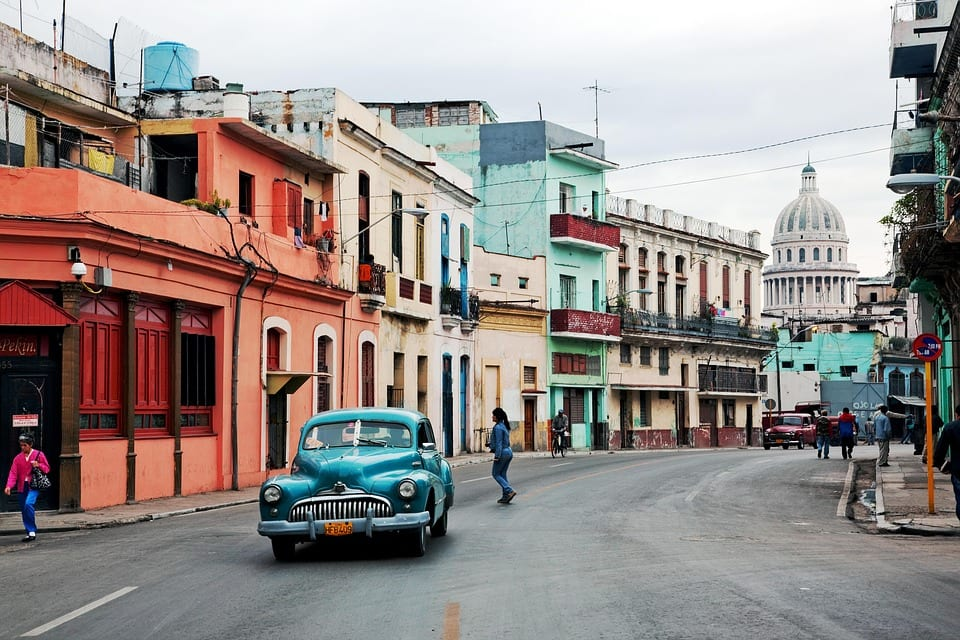 A brightly colored classic American car drives along a street in Cuba, with a background of tropical-hued two-story buildings.