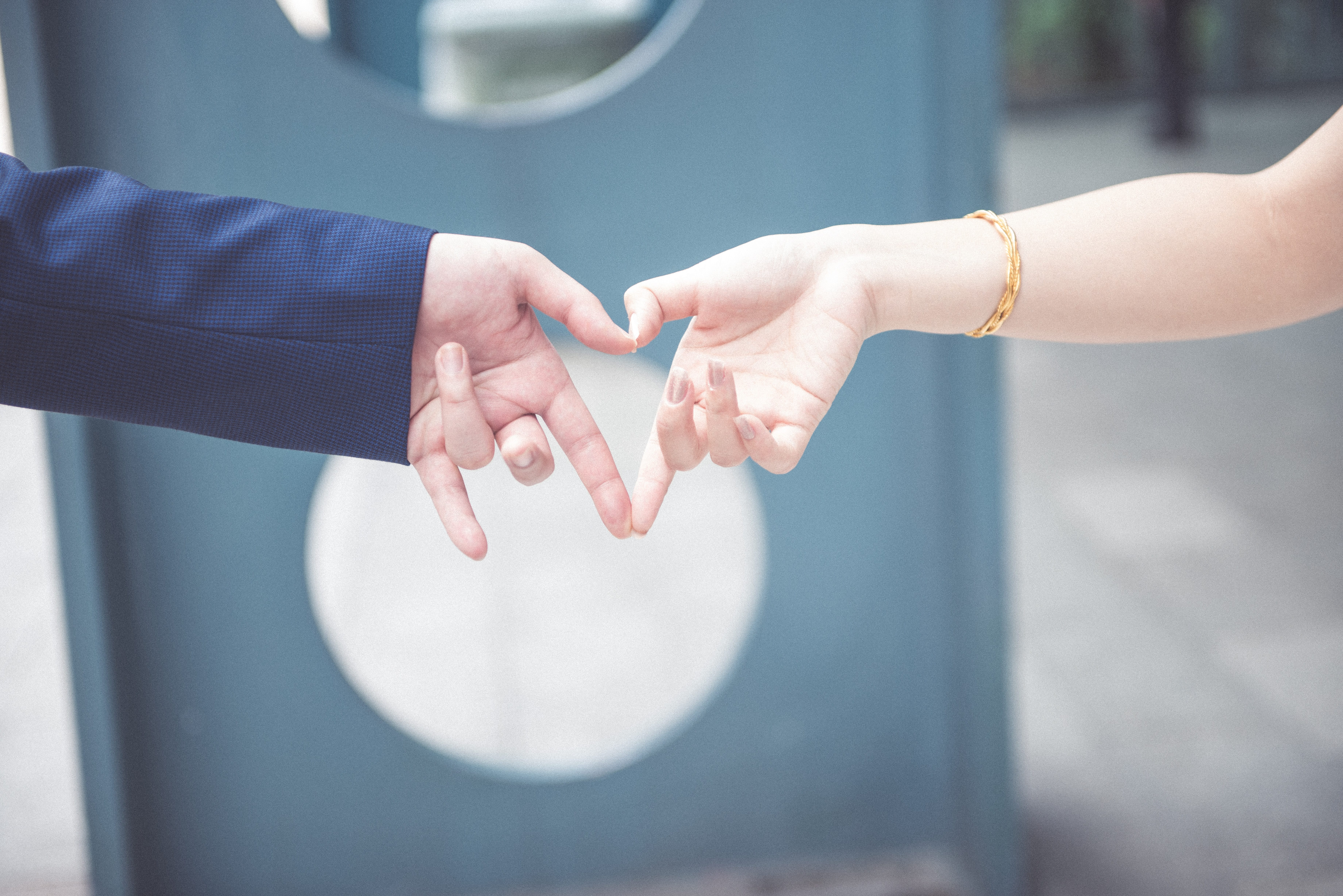 Man and woman making heart symbol with hands; image by Han Hsing Tu, via Unsplash.com.