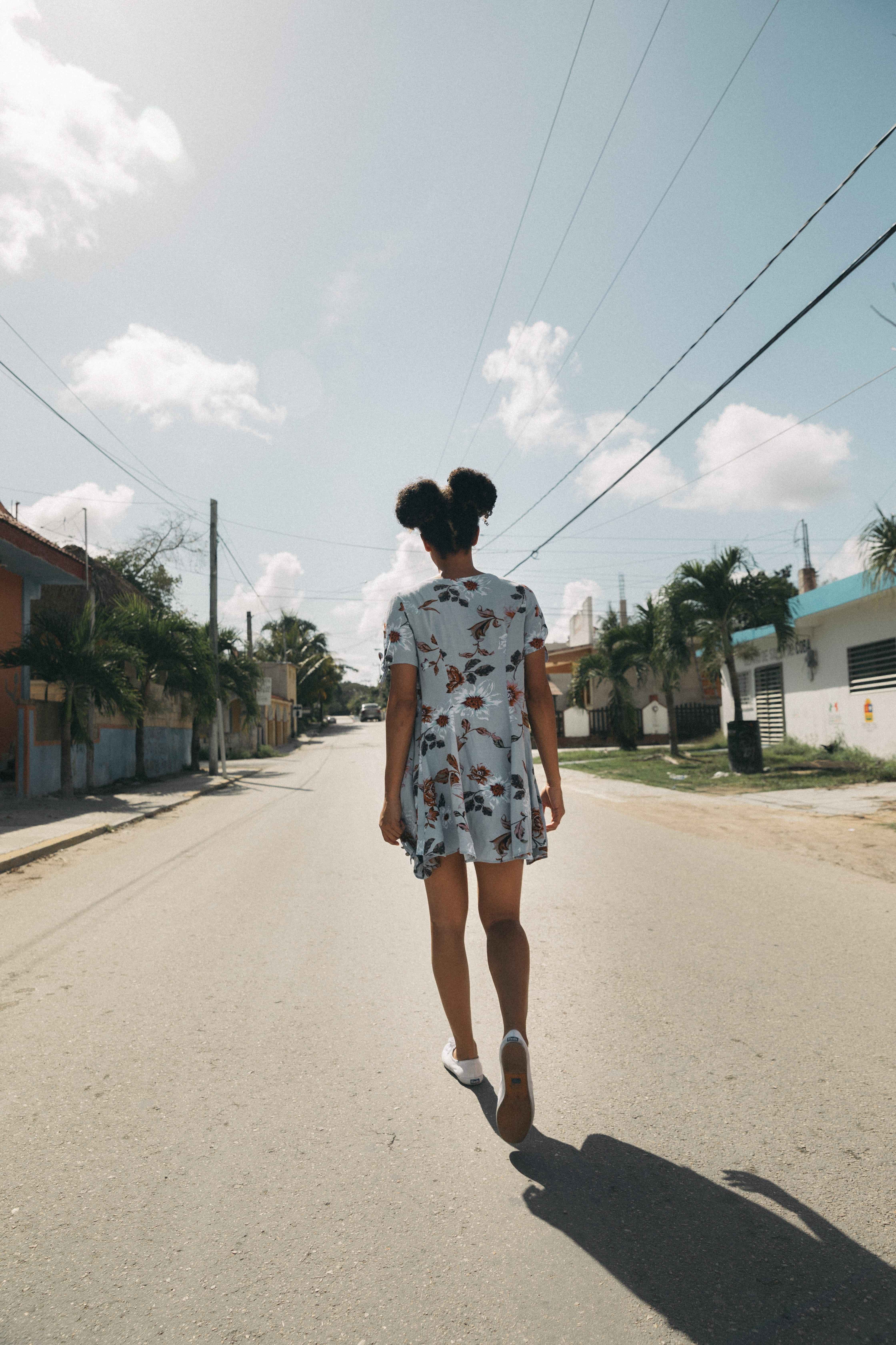 Young African-American woman in a sundress walking away from the camera; image by Jakob Owens, via Unsplash.com.