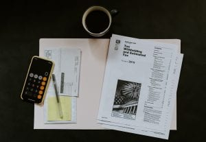 Tax withholding and estimated tax paperwork near a smartphone calculator, pen, paper, and coffee; image by Kelly Sikkema, via Unsplash.com.