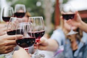 People toasting each other with glasses of red wine; image by Kelsey Knight, via Unsplash.com.