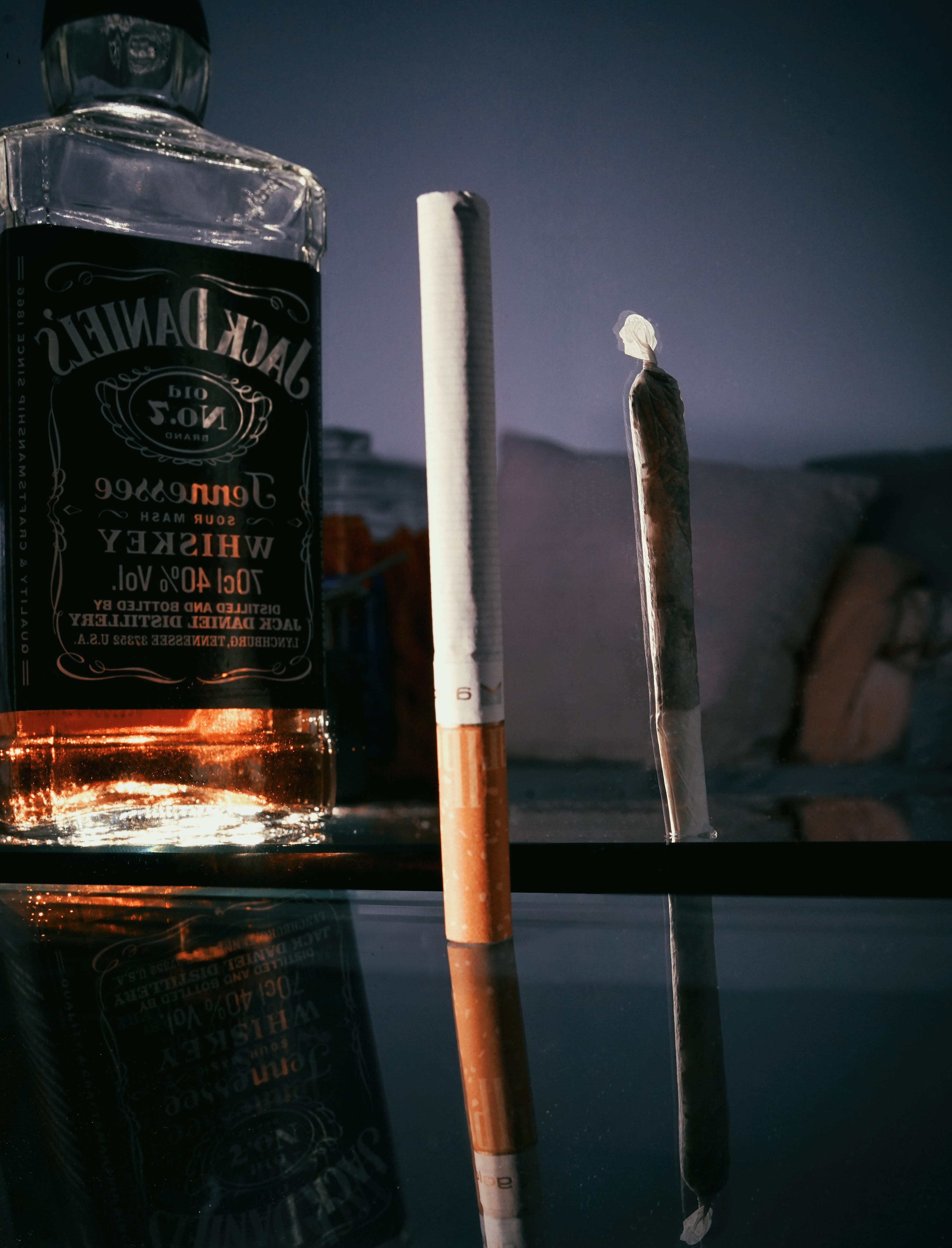 Bottle of Jack Daniels whiskey next to a cigarette and a joint; image by Marc Schaefer, via Unsplash.com.