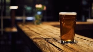 Glass of beer on wooden table; image by mnm.all, via Unsplash.com.