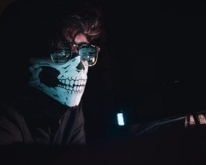 Man wearing a skull mask and reflective glasses in a dark room. Computer code is reflected in his glasses. Image by Nahel Abdul Nadi, via Unsplash.com.