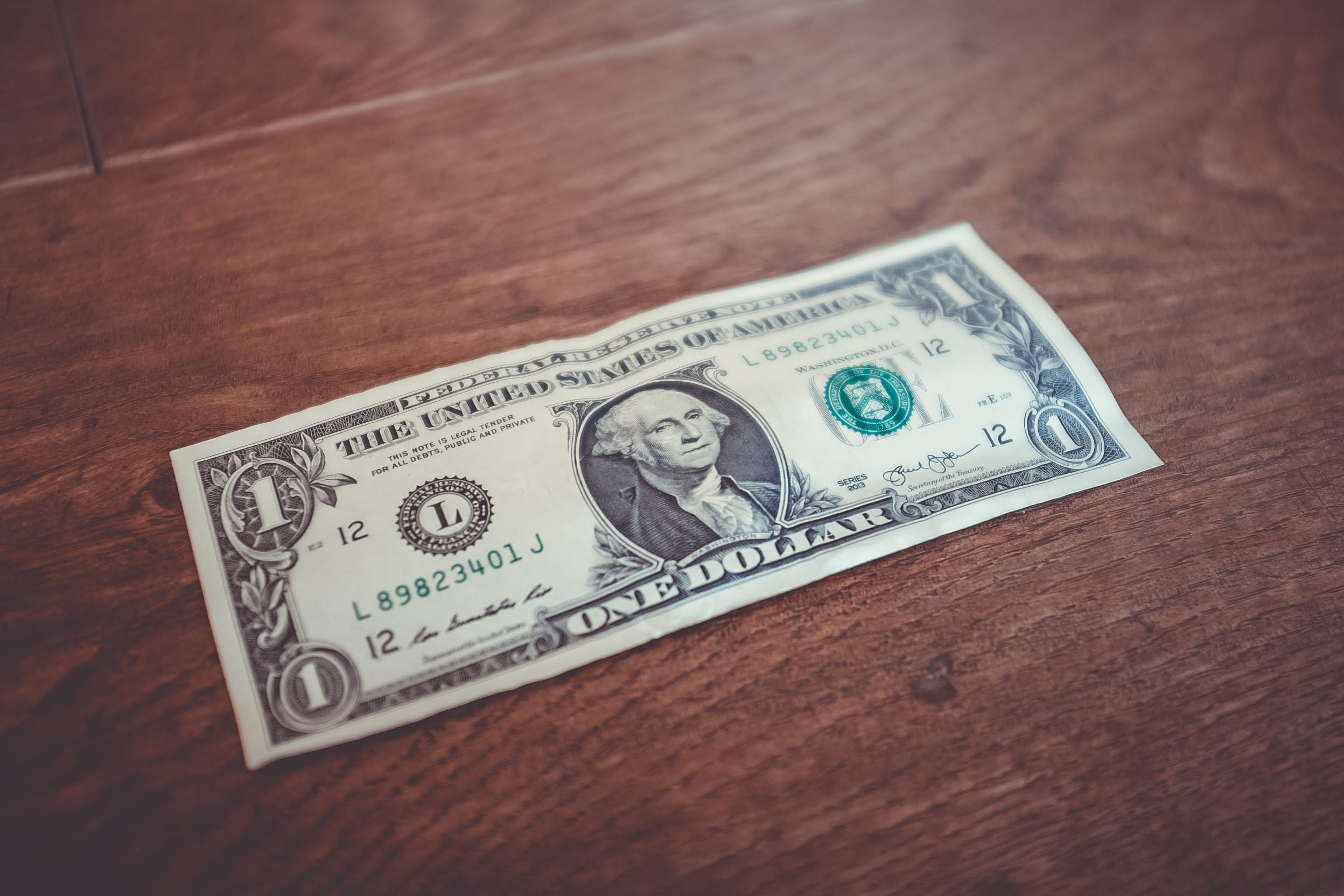 A one-dollar bill on a brown wooden table; image by NeONBRAND, via Unsplash.com.