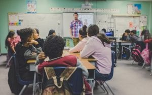 Classroom with teacher at front; image by NeONBRAND, via Unsplash.com.