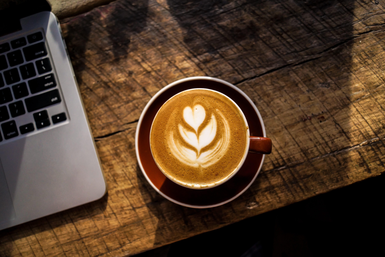 Latte with foam design of heart-shaped flower on table near laptop; image by Nolan Issac, via Unsplash.com.