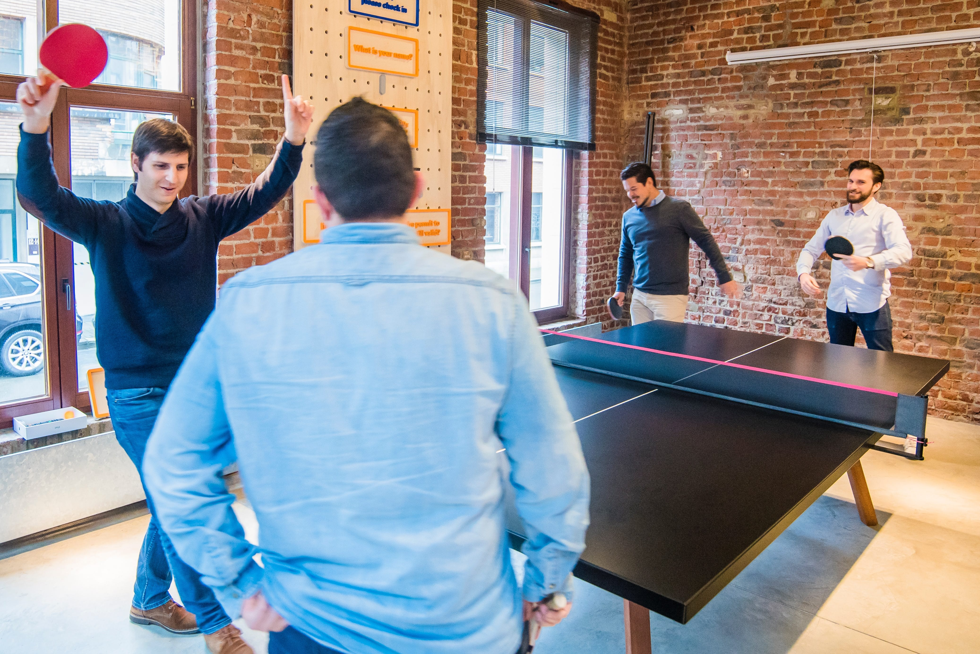 Four men playing table tennis; image by Proxyclick Visitor Management System, via Unsplash.com.