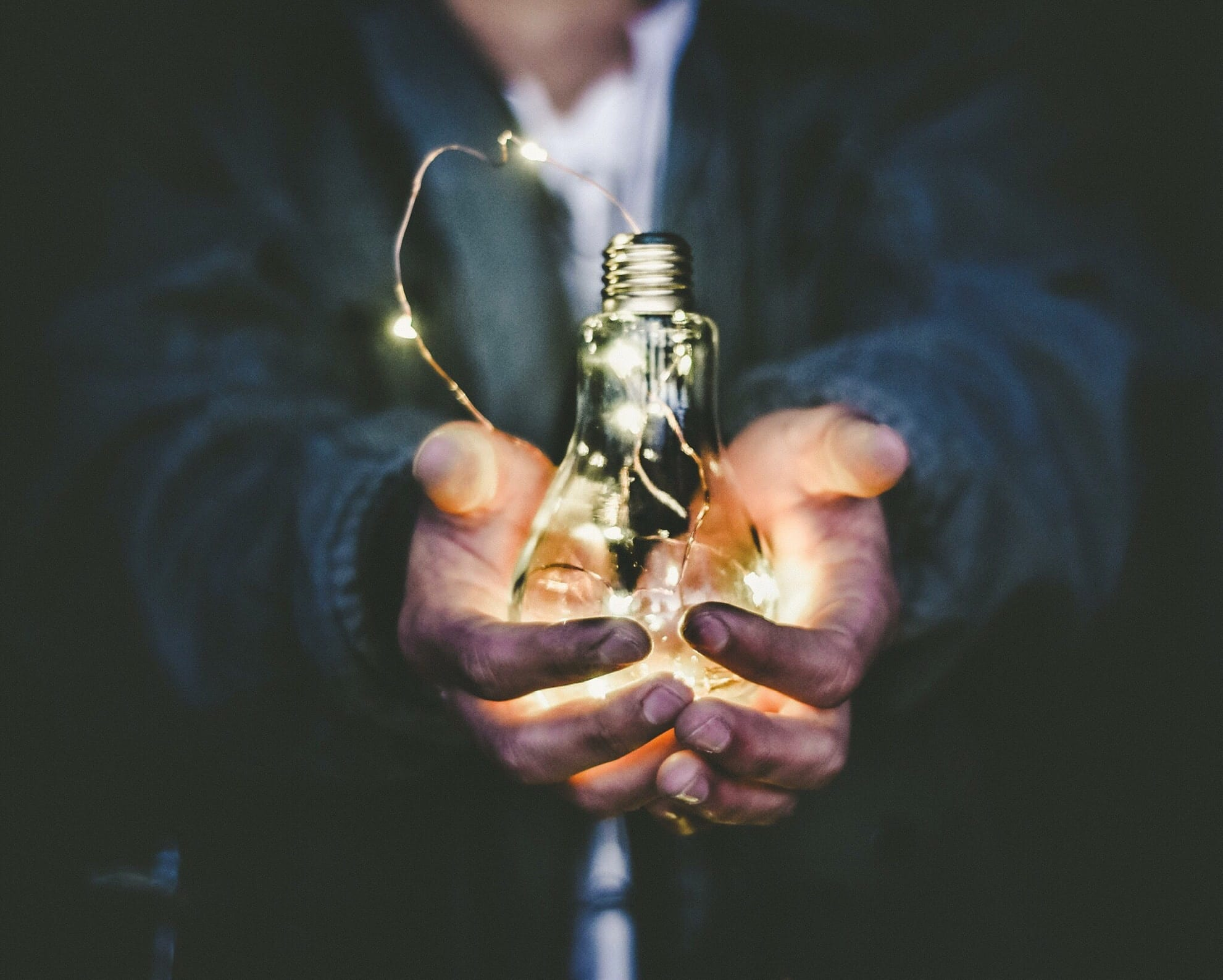 Man holding lit light bulb in outstretched hands; image by Riccardo Annandale, via Unsplash.com.