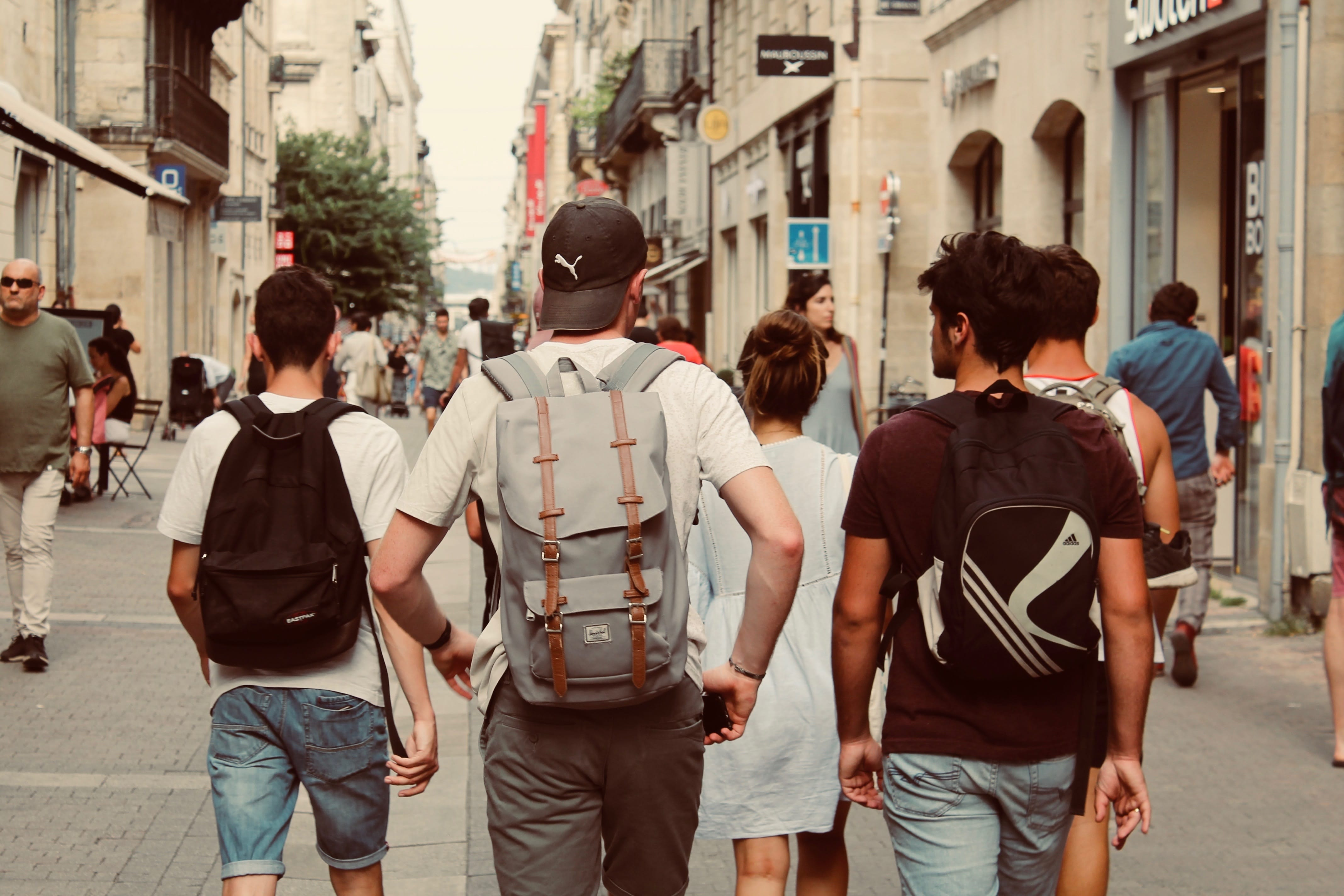 Group of teenagers wearing backpacks walking away from camera; image by Rich Smith, via Unsplash.com.