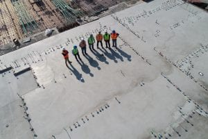 Seven construction workers standing on a white field; image by Scott Blake, via Unsplash.com.