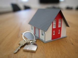 Red, white and grey toy house sitting on table next to house key on keyring shaped like a house; image by Tierra Mallorca, via Unsplash.com.