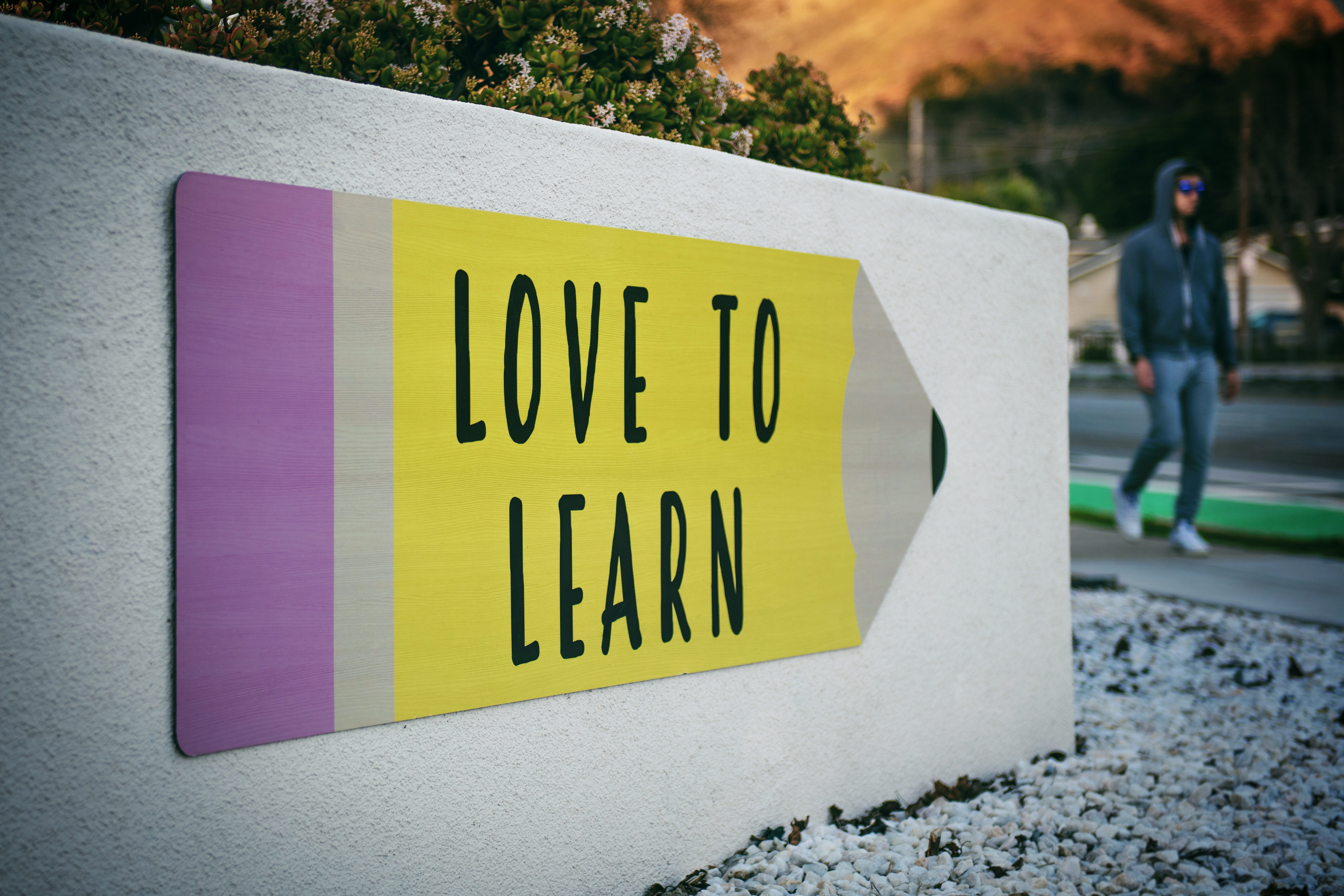 """Love to learn"" pencil signage on wall near walking man; image by Tim Mossholder, via Unsplash.com."