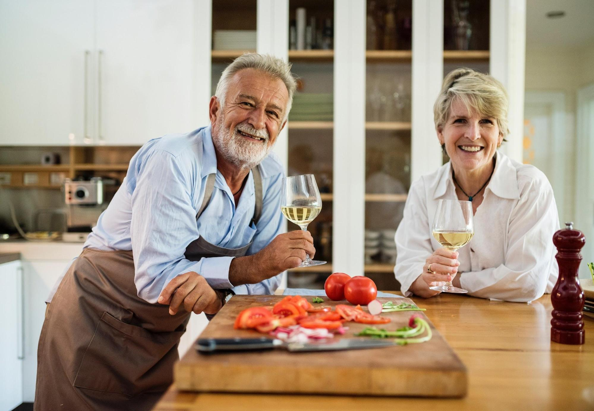 Older man and woman in kitchen with tomatoes on cutting board, drinking wine; image via Pexels.com.
