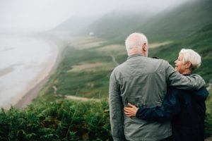 Older man and woman looking over a beach scene; image via Pexels.com.