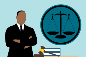 Graphic depicting African-American man in suit with arms folded, standing near a desk on which sits a gavel. The scales of justice are on the wall behind the desk. Graphic by Mohamed Hassan, via pxhere.com, CC0 public domain.
