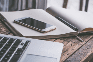 Laptop next to a smartphone sitting on top of an open notebook with a pen, all on a wooden table; image by 6689062, via Pixabay.com.