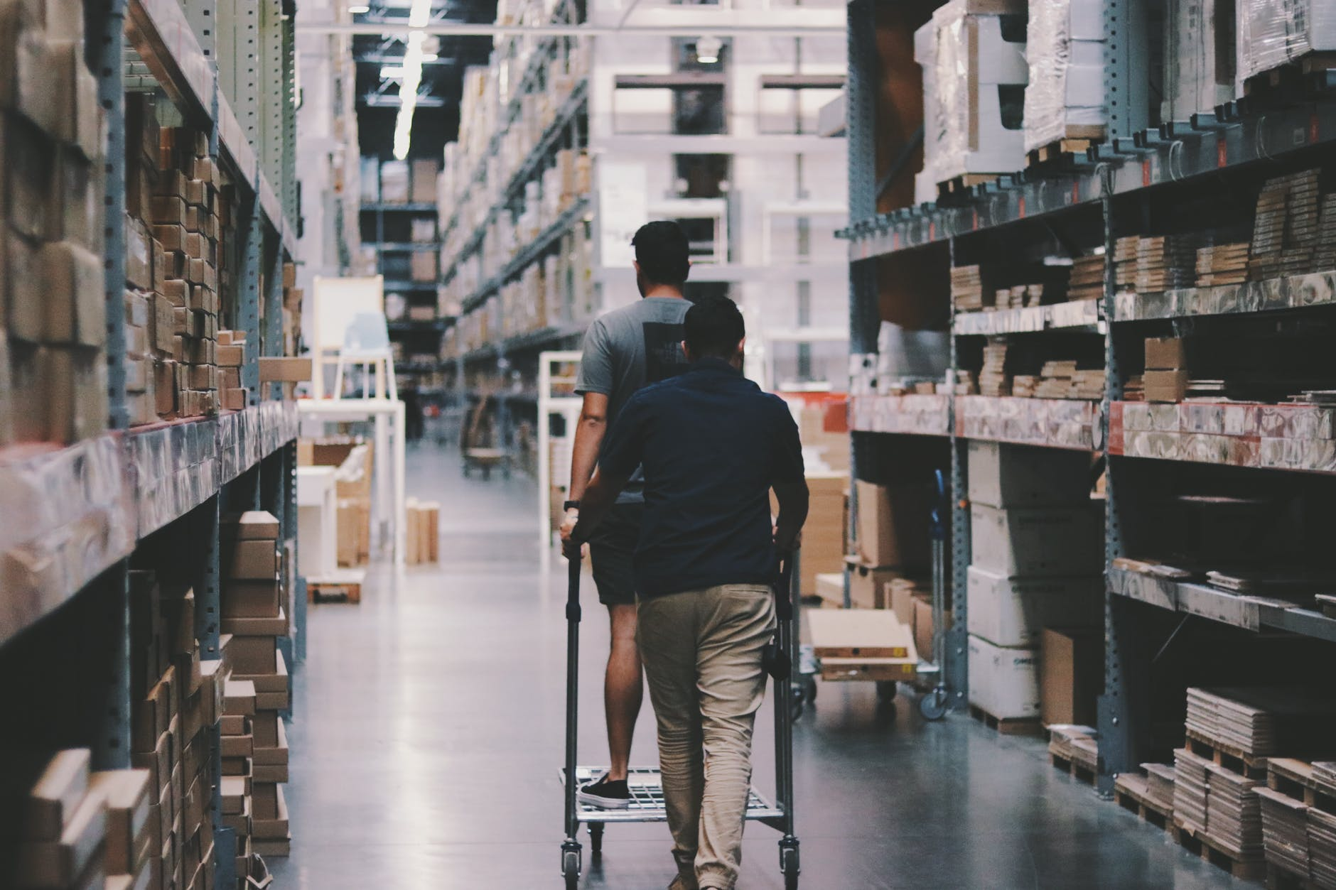 Two men, one on a cart & one pushing it, going through a warehouse; image by Alexander Isreb, via Pexels.com.