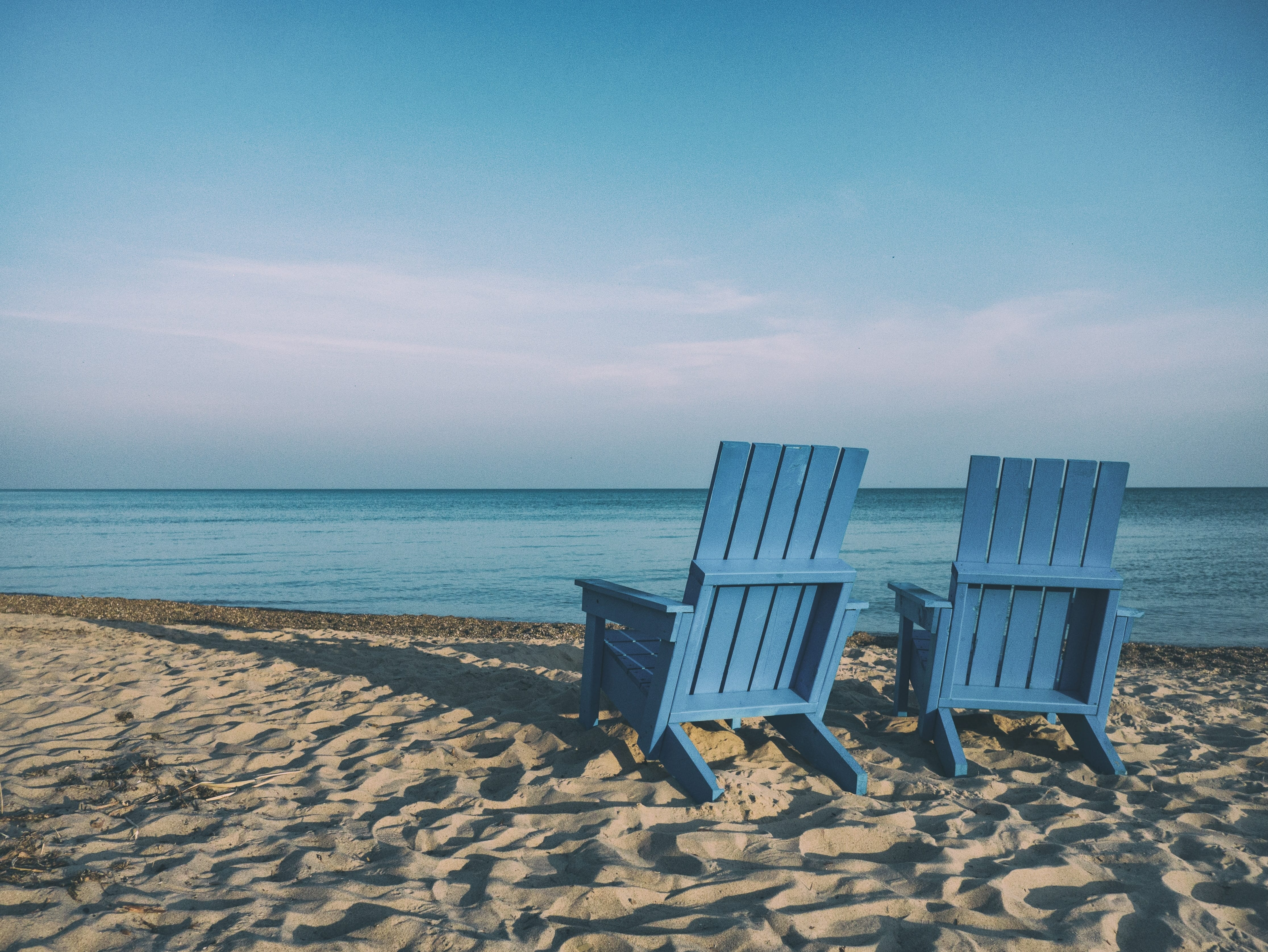 Two blue Adirondack chairs on the beach; image by Aaron Burden, via Unsplash.com.