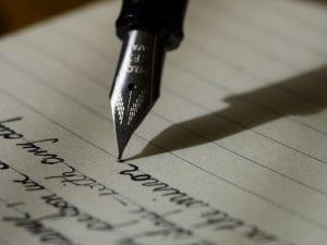 Fountain pen on black lined paper; image by Aaron Burden, via Unsplash.com.