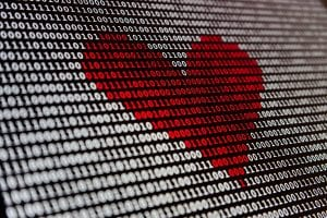 Computer screen showing binary code in white with some in red in the shape of a heart; image by Alexander Sinn, via Unsplash.com.