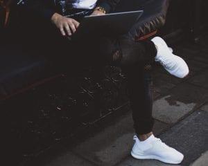 Man in black jeans with legs crossed using laptop; image by Alexandra K, via Unsplash.com.