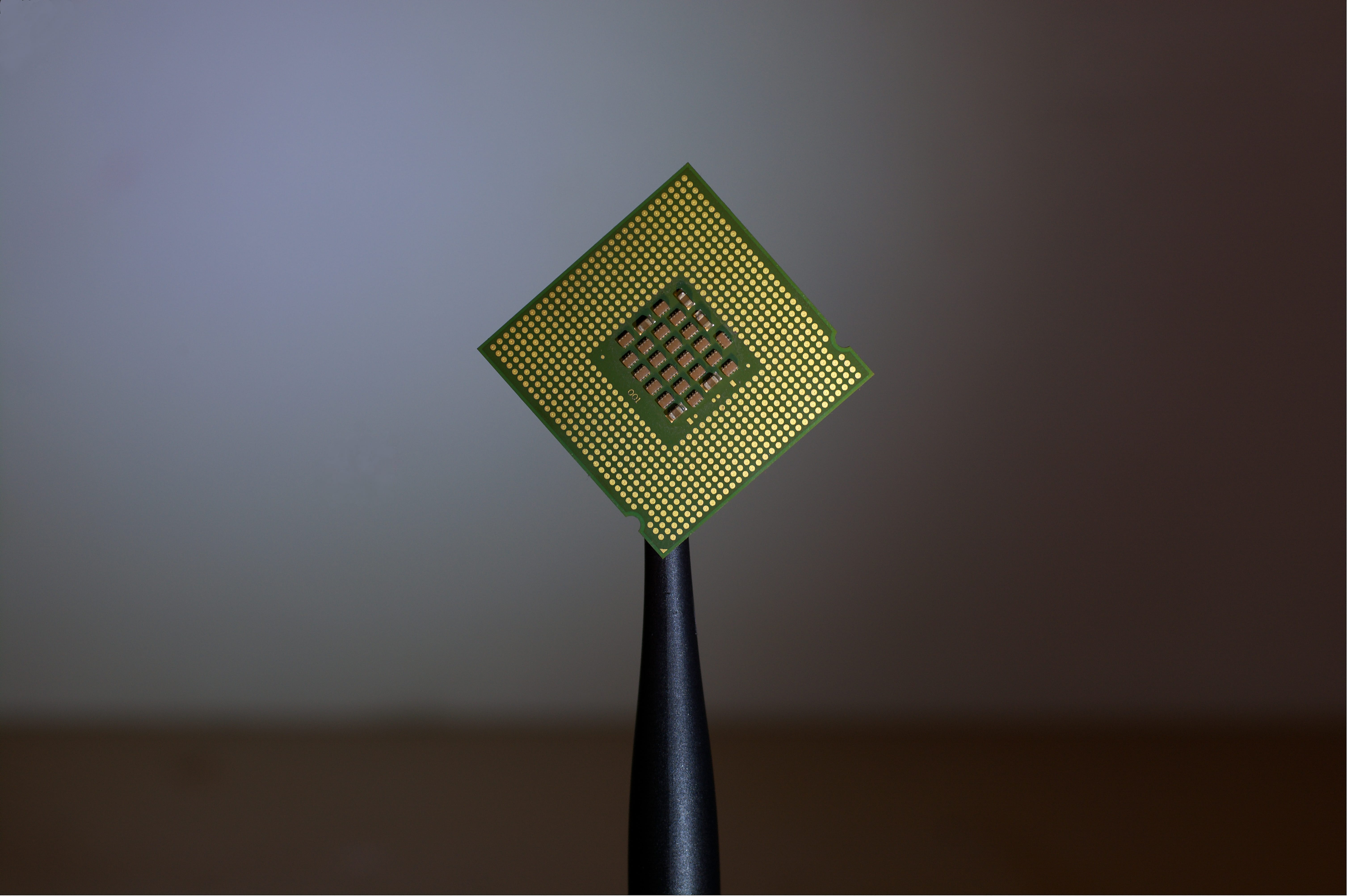 Green and gold computer chip; image by Brian Kostiuk, via Unsplash.com.