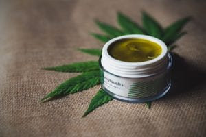 White container of CBD on top of hemp leaf, both on a burlap surface; image by CBD Infos, via Unsplash.com.