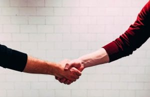 Two men shaking hands in front of a white tiled wall; image by Chris Liverani, via Unsplash.com.