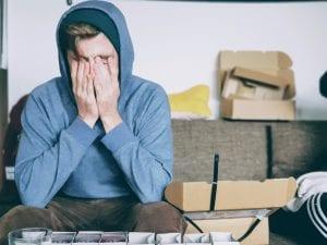 Man in blue hoodie sitting on sofa; image by Christian Erfurt, via Unsplash.com.