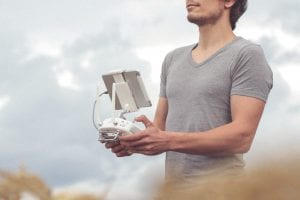 Man holding white and gray drone controller; image by Christian Langenhan, via Unsplash.com.