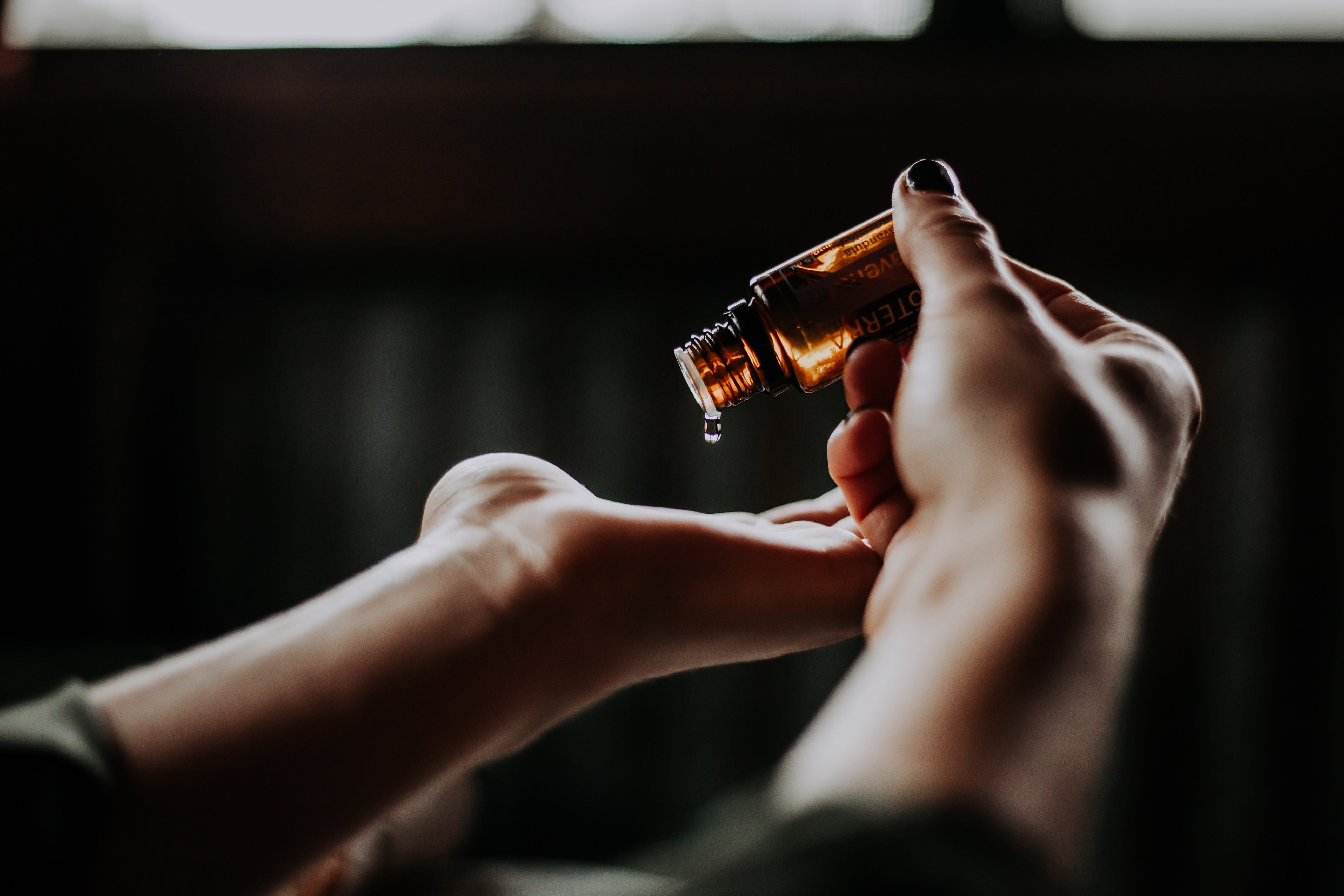 Woman holding amber glass bottle and pouring a drop of oil into her open palm; image by Christin Hume, via Unsplash.com.