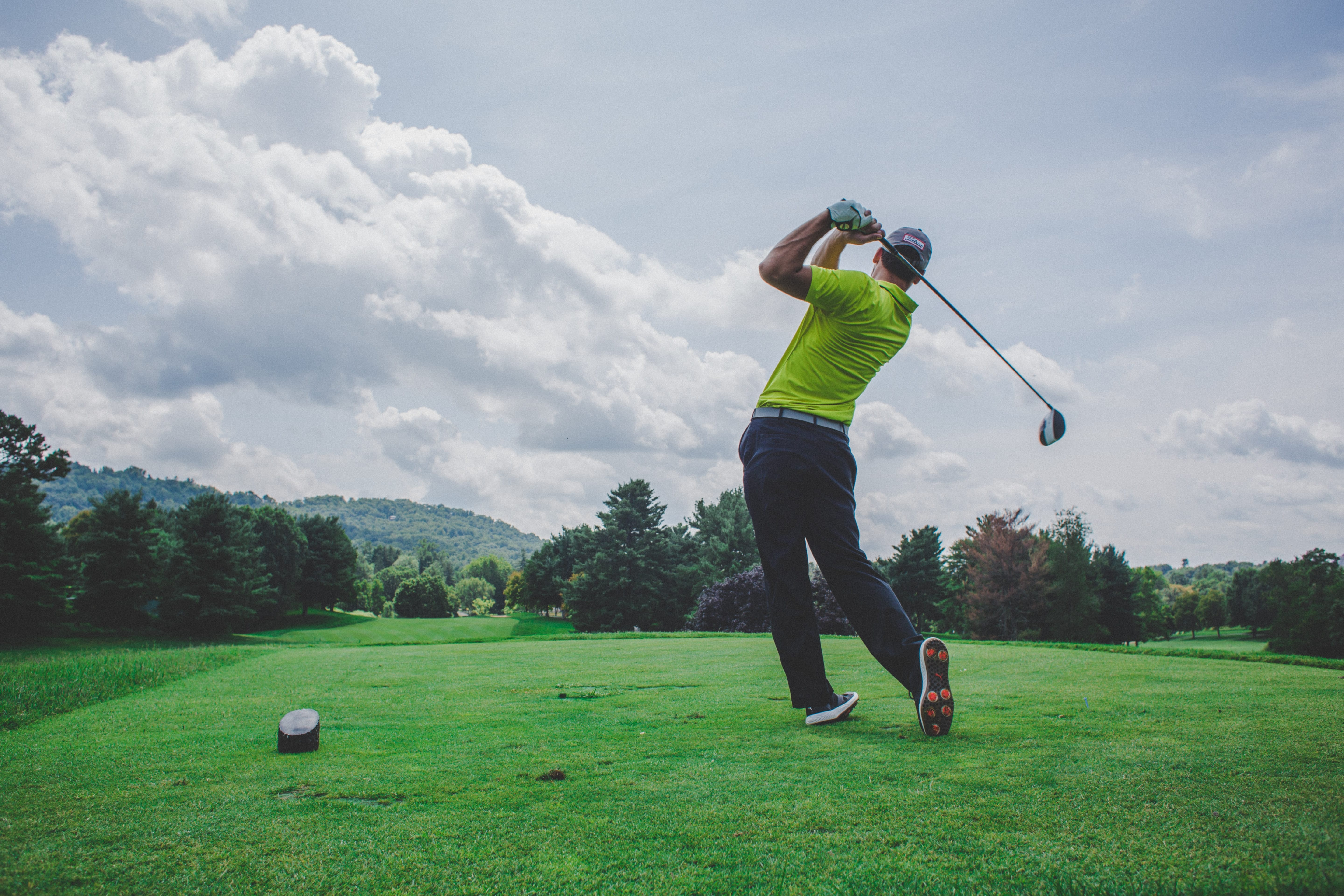 Man hitting golf ball on course; image by Court Cook, via Unsplash.com.
