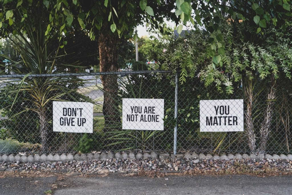 "Three signs on a chain link fence, reading (in order) ""Don't Give Up,"" ""You Are Not Alone,"" and ""You Matter."" Image by Dan Meyers, via Unsplash.com."