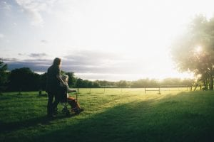 Woman standing next to woman riding wheelchair on grass in the sun; image by Dominik Lange, via Unsplash.com.