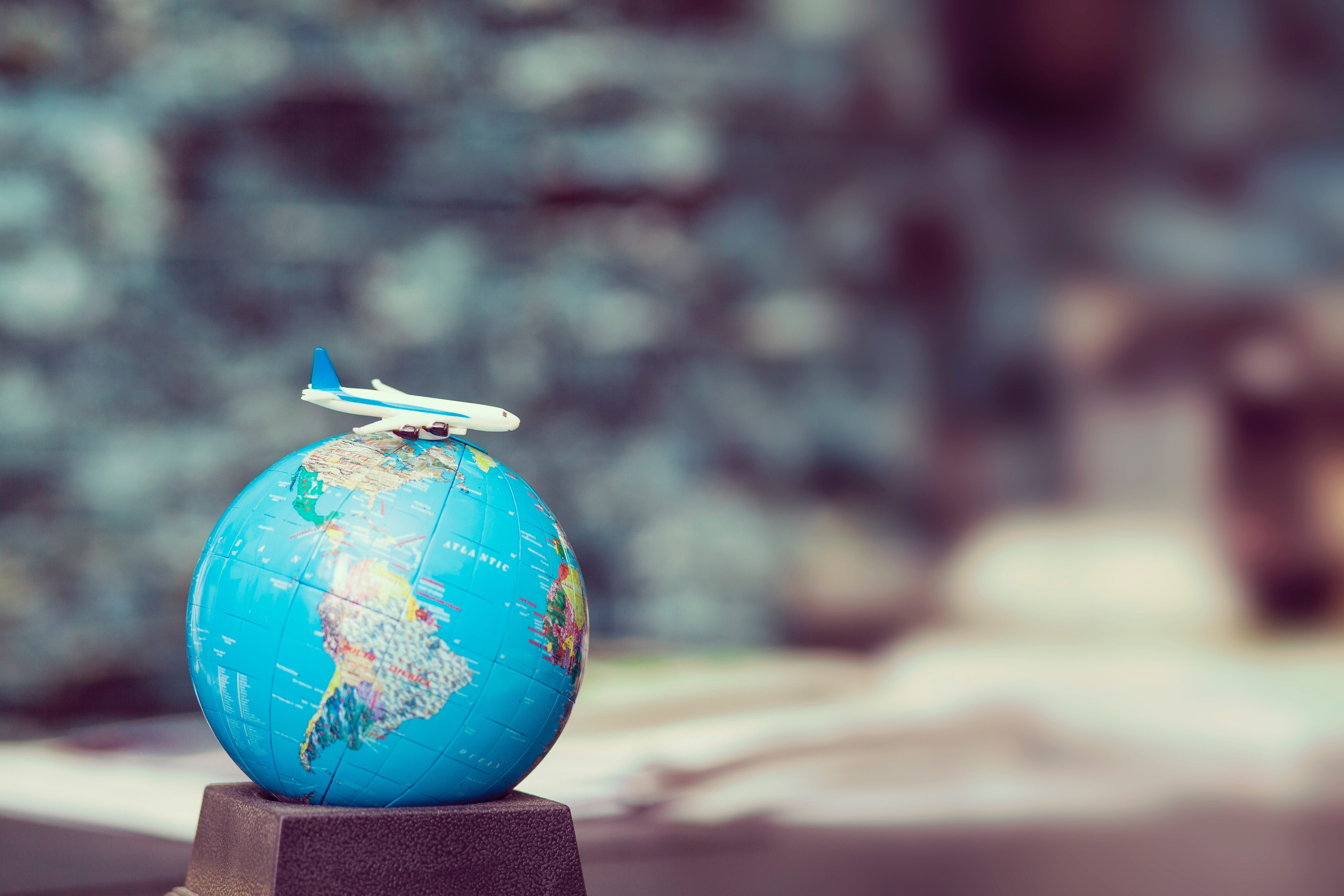 Selective focus shot of globe with airplane on desk; image by Frank Vex, via Unsplash.com.