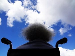 Rear view of woman in wheelchair looking at blue sky with clouds; image by James Williams, via Unsplash.com.