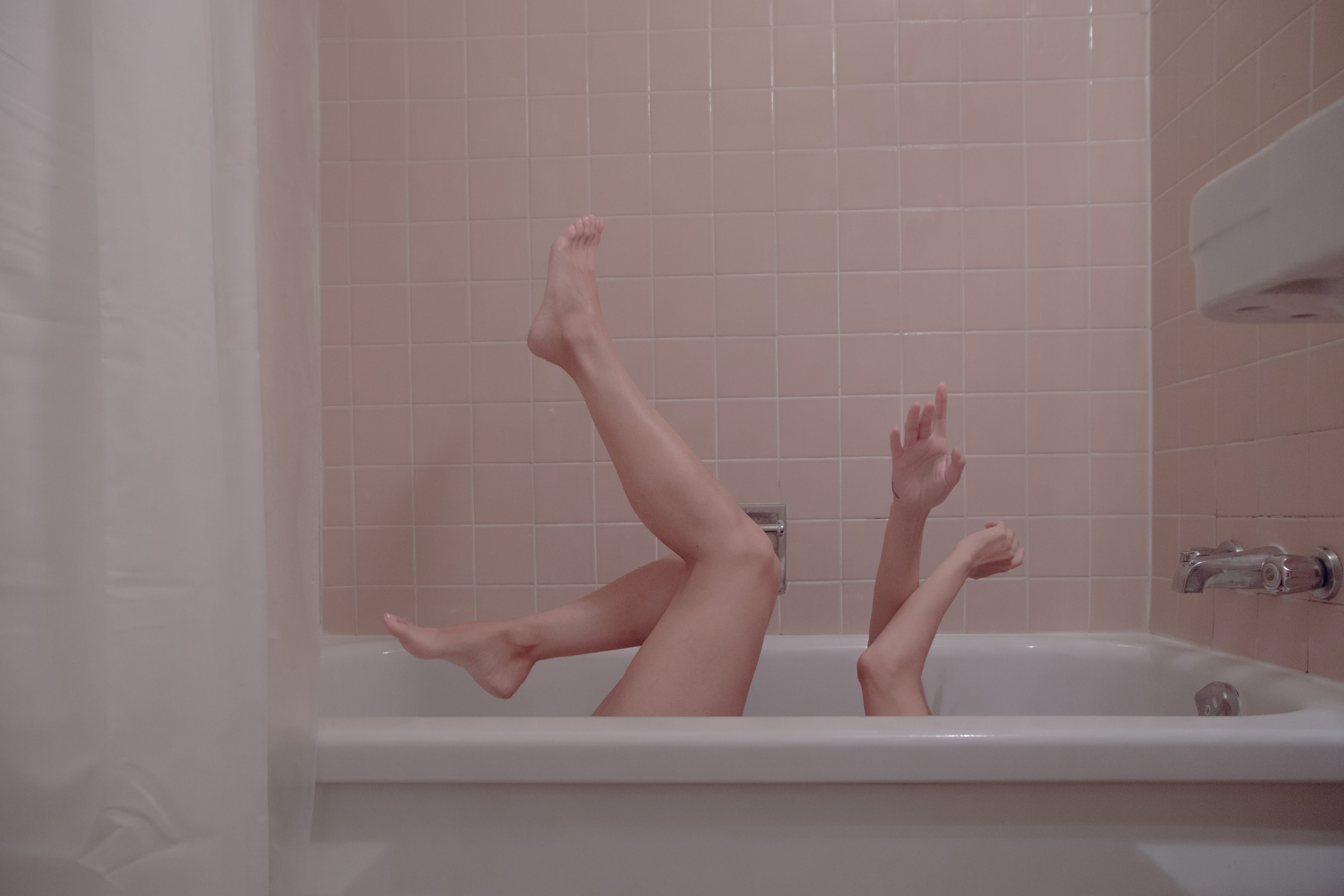 Woman's arms and legs protruding from white bathtub as she is on her back; image by Julieta Christy, via Unsplash.com.